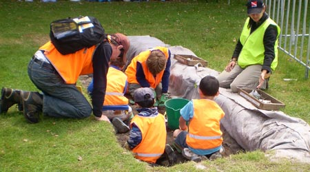 Children working in an archaeological trench with a father leaning over the edge looking on.